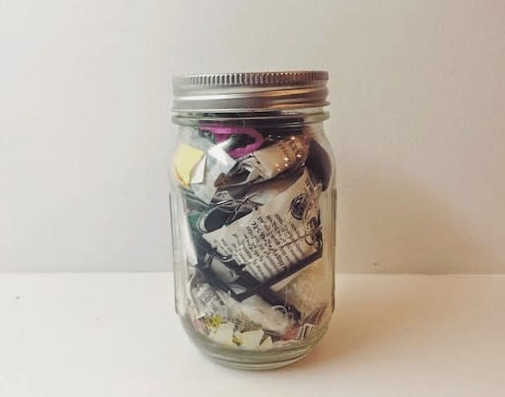 Papers in jar on table