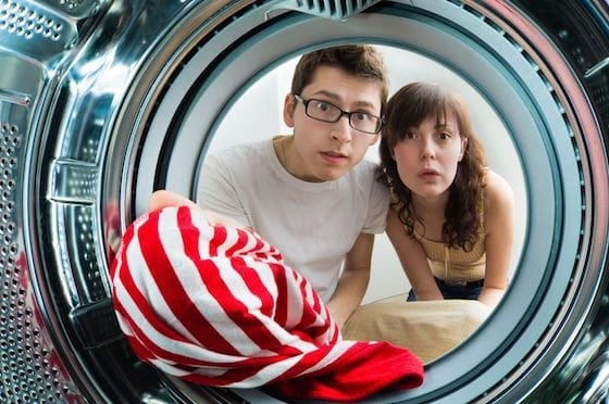 Young couple peering into clothes dryer with worry