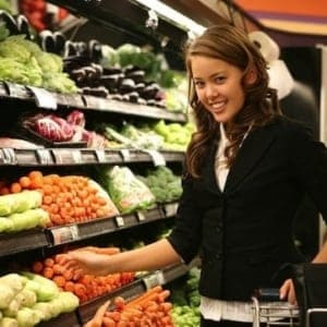 A woman standing in front of a store filled with lots of fresh produce