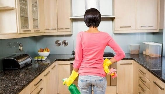 Woman with cleaning supplies ready to clean kitchen cabinets