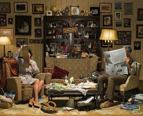 man-and-woman-sitting-in-a-room-overtaken-clutter.jpg