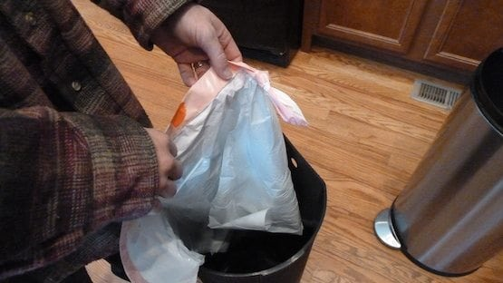 How to insert tied trash bag