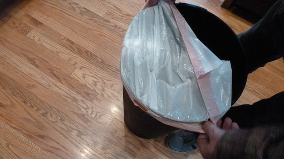 Final step of putting trash bag into trash can