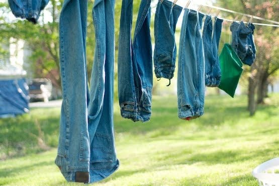 Blue jeans hanging on a cloths wire outside