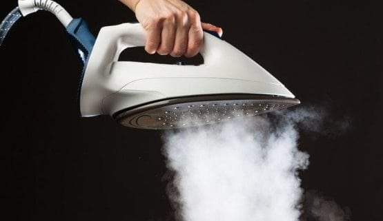 woman-holding-steam-iron-that-is-making-tons-of-steam!