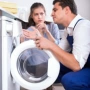 Repairman looking at washing machine to give woman an estimate to repair