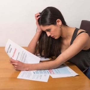 Young woman perplexed looking at her student loan documents