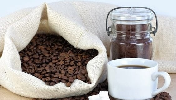 Coffee beans in a bag, ground coffee in a jar, brewed coffee in a cup