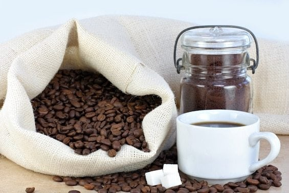 Coffee beans in a bag, ground coffee in a jar and brewed coffee in a cup