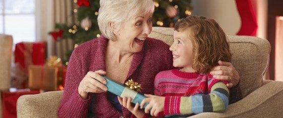 Girl giving grandmother Christmas gift