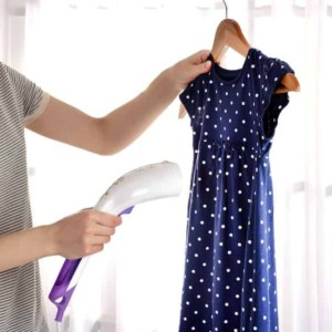Woman releasing wrinkles from a blue polka dot dress with garment steamer
