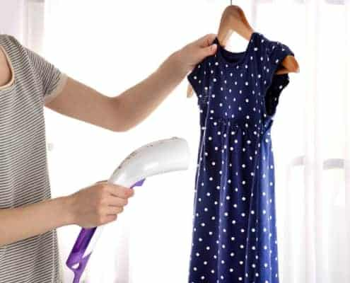 A person wearing a blue dress standing in front of a curtain