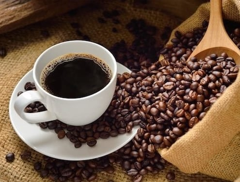 A cup of coffee on a table, with Coffee bean