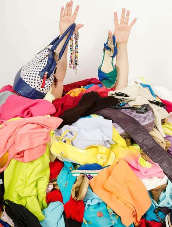 Woman buried under piles of disorganized clothes shoes and bags