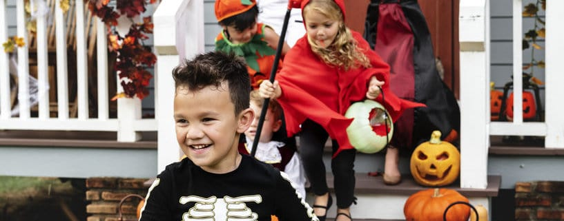 Young kids in costume trick or treating during Halloween