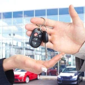 Salesman handing female customer key to new car