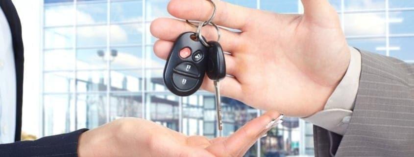 Salesman handing female customer key to new car