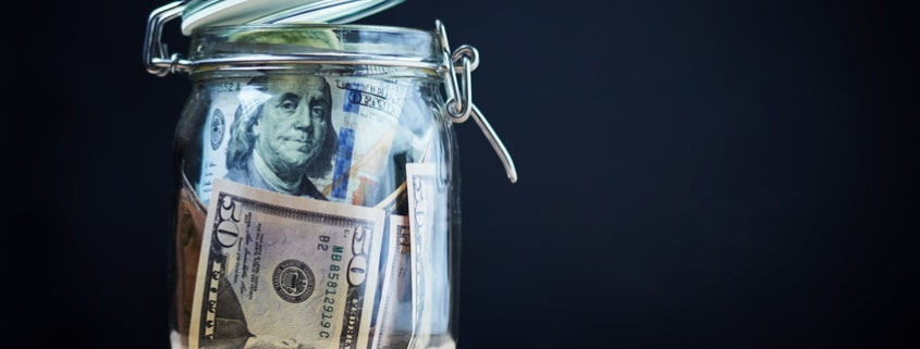 US Dollar bills in glass jar suggesting cash stash