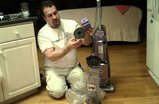 Man sitting on floor taking a Shark vacuum apart to clean it
