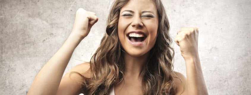 Young woman with killer credit score super happy with two fists in the air