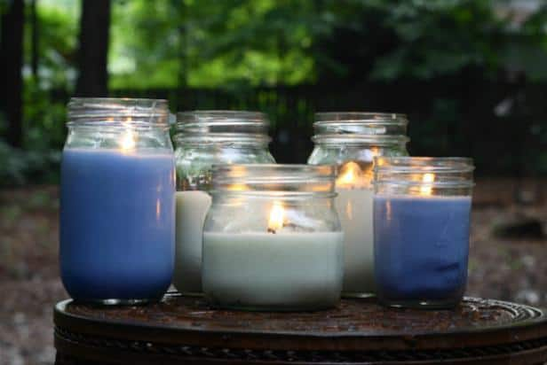 Lit candles in jars in both blue and white