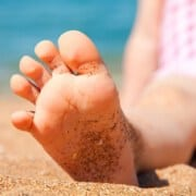 Child's foot with beach sand.