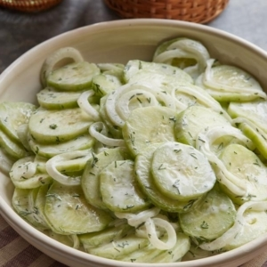 A bowl of food on a plate, with Cream and Cucumber