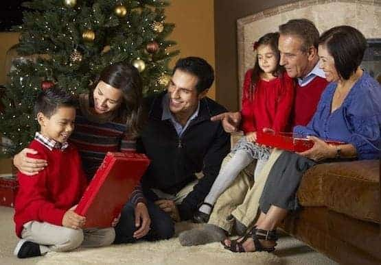 Family sitting around christmas tree opening gifts