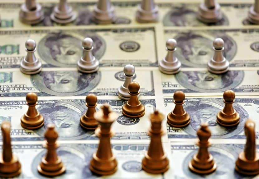 a chess board covered in US five dollar bills with chess pieces in play