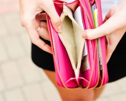 Woman opening bright pink wallet to discover complete lack of money