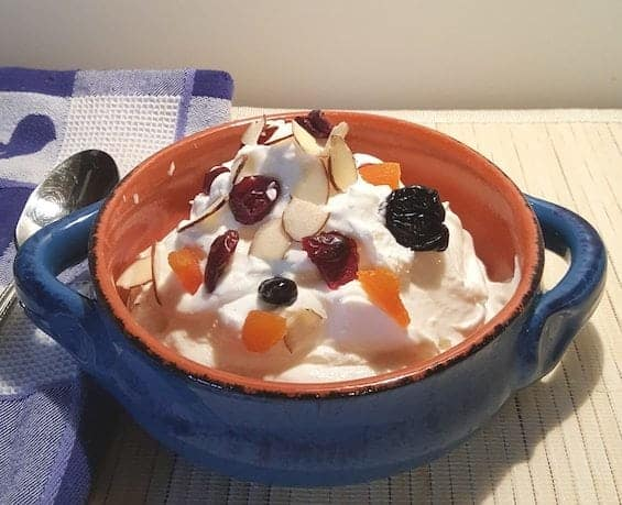 A bowl of fruit on a plate, with Yogurt and Microwave oven