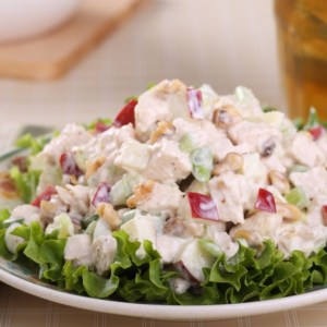 A close up of a bowl of salad, with Chicken and Teaspoon