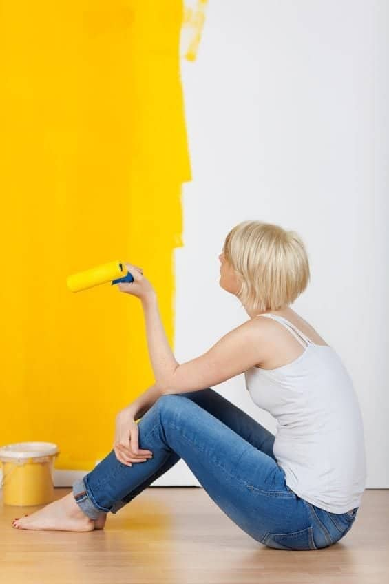 young-casual-woman-with paint roller sitting on floor and looking-at-half-yellow-painted-wall