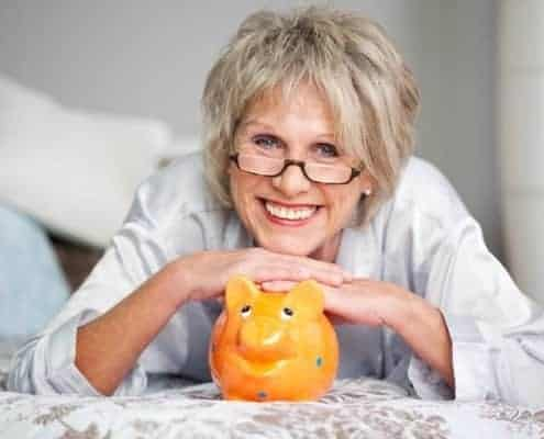 Conceptual portrait of happy senior female with piggybank