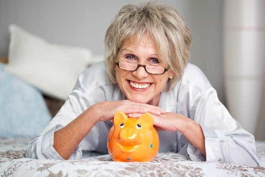Conceptual portrait of happy senior female with piggybank