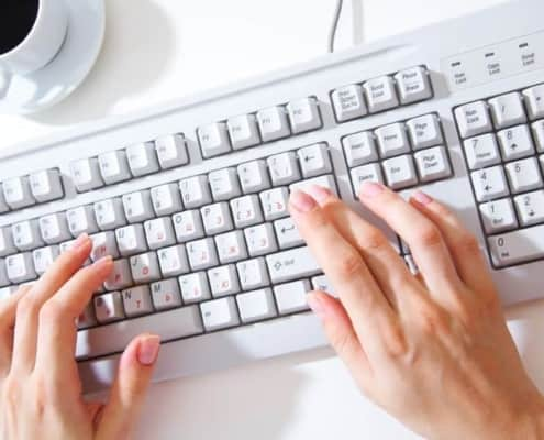 A person using a laptop computer sitting on top of a keyboard