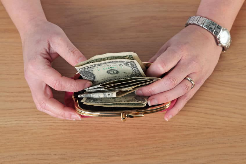 overhead-close-up-photo-of-a-woman-putting-money-into-her-purse