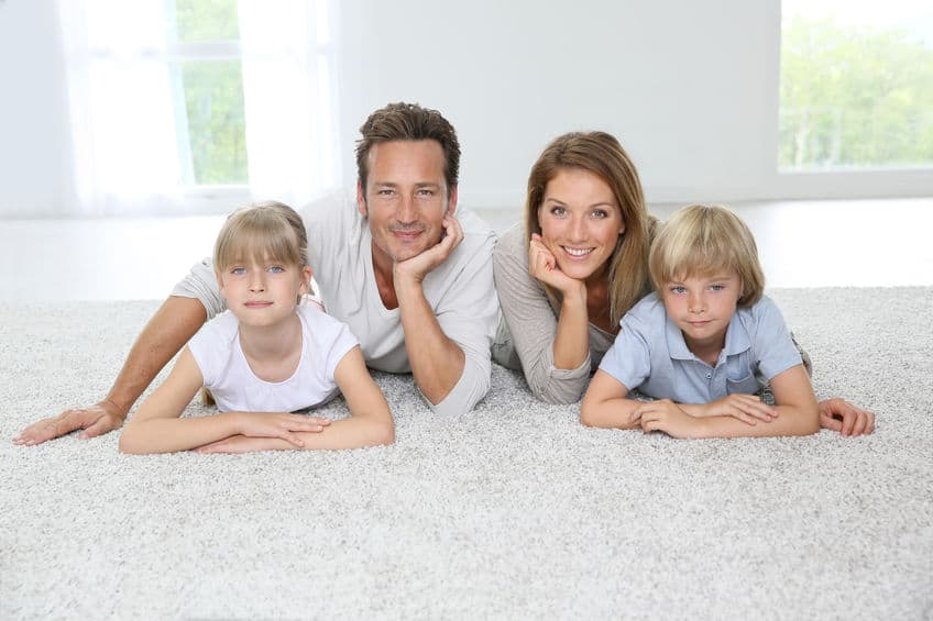 Happy family of four in love with their clean carpet