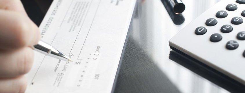 Grandparent writing a check as gift for college-bound grandchildd