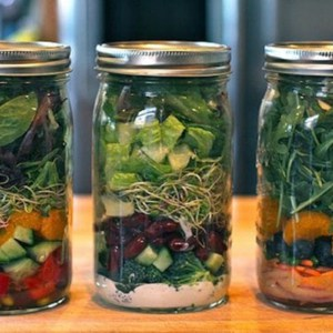 3 canning jars with salad ingredients layered inside