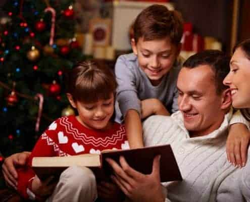 Modern family of four reading Christmas stories