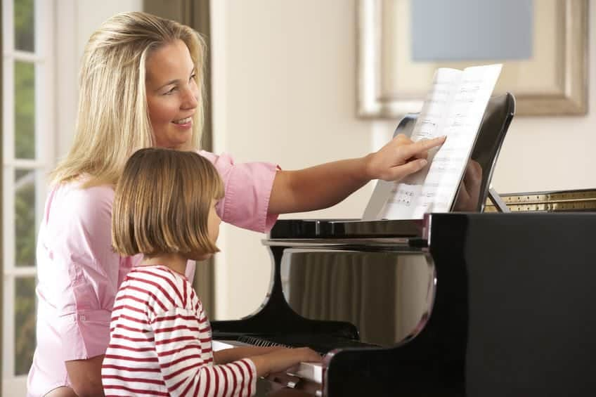 piano-teacher-young-girl-student-at-piano