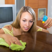 Young woman polishing table with homemade furniture polish