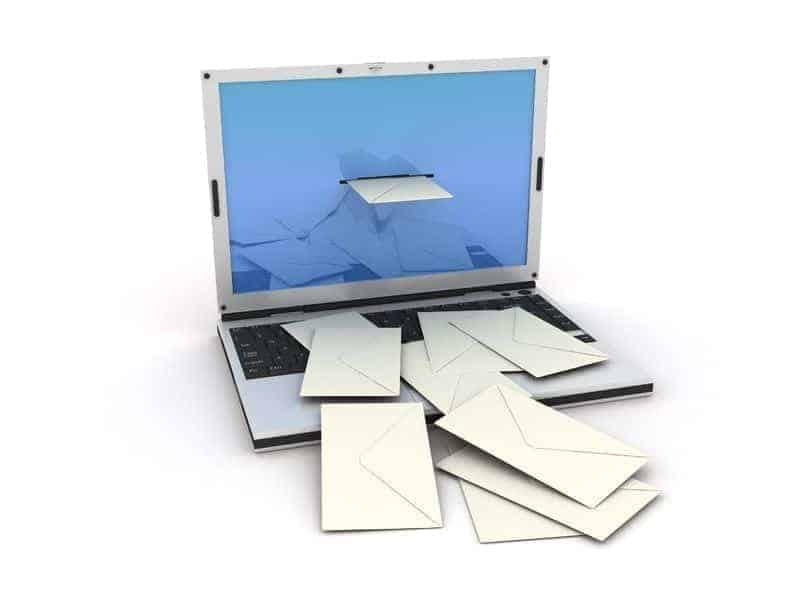 laptop with mail arriving in form of letters in envelopes.
