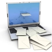 Laptop computer illustrating email by envelopes coming out of the screen