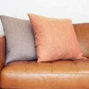 Learn to clean this tan leather sofa with two fabric pillows