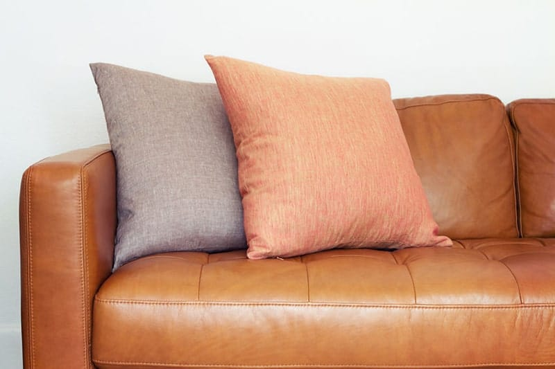 A brown leather couch sitting on top of a chair