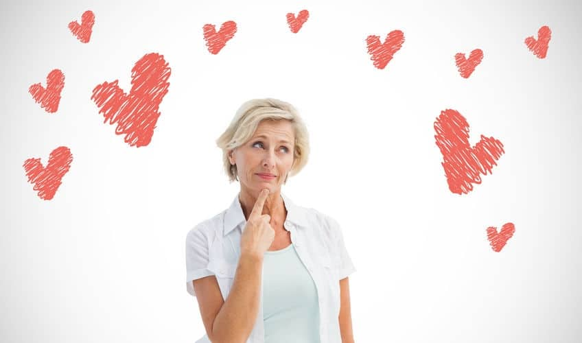 Mature woman thinking with hand on chin against white background with Valentine's Day vignette