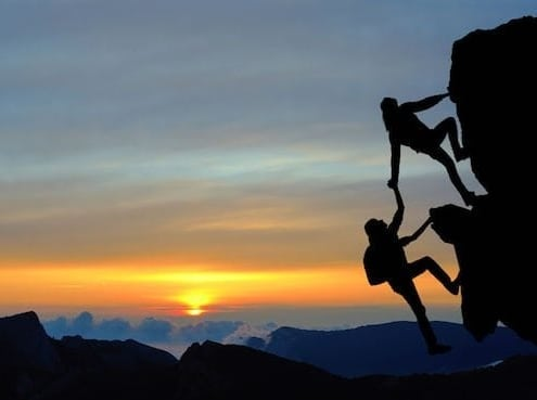 mountain-climber-helping-companion-reach-the-top