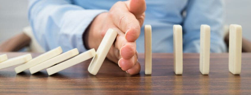 Woman stopping the domino effect suggesting she's breaking a bad habit